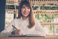 开始在咖啡馆的妇女工作 女学生在noteb写笔记 免版税库存图片