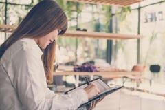 开始在咖啡馆的妇女工作 女学生在noteb写笔记 库存图片