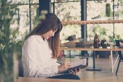 开始在咖啡馆的妇女工作 女学生在noteb写笔记 免版税库存照片