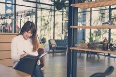 开始在咖啡馆的妇女工作 女学生在noteb写笔记 免版税图库摄影