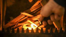 开始在火炉的火,有点燃堆木柴的打火机的男性手 库存照片