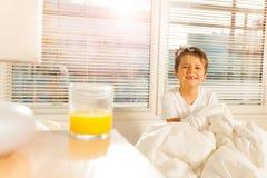 开始愉快的男孩他的与杯的早晨汁液 免版税库存照片