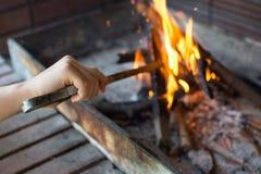 开始木炭格栅的火 有长柄的钳子Se的胳膊 免版税库存照片