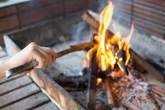 开始木炭格栅的火 有长柄的钳子Se的胳膊 免版税库存图片
