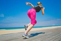 开始状态的女运动员准备好跑 少妇准备好体育在海滩行使 运动的妇女 库存照片