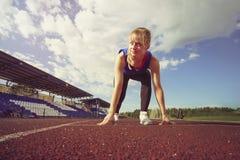 开始状态的种族适合的确信的妇女准备好跑 开始短跑的女运动员看  免版税库存照片