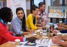 开始见面 在书桌屏幕的后面有新的办公室设计的(颜色:绿色、灰色和beig 库存照片