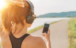 开始跑步和听到音乐的年轻少年女孩使用智能手机和无线耳机 免版税库存照片
