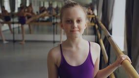 开始跳芭蕾舞者的美丽的小女孩画象看照相机和微笑的站立在芭蕾类  股票录像
