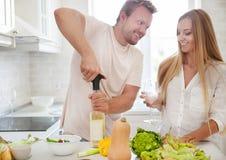 开始年轻的夫妇在家喝白葡萄酒 库存图片