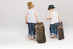 离开带着他们的手提箱的两个逗人喜爱的兄弟 库存图片