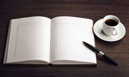 开张在服务台上的一份空白空白笔记本、笔和咖啡 免版税库存照片