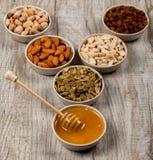 开心果、杏仁、花生、南瓜籽、葡萄干和蜂蜜在陶瓷板材 免版税库存图片
