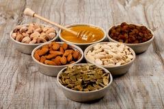 开心果、杏仁、花生、南瓜籽、葡萄干和蜂蜜在陶瓷板材 免版税库存照片