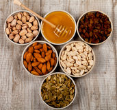 开心果、杏仁、花生、南瓜籽、葡萄干和蜂蜜在陶瓷板材 库存图片