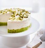 开心果乳酪蛋糕,在一块白色板材的奶油甜点蛋糕 库存照片