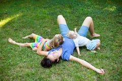 开心的快乐的家庭放置在草在公园 免版税库存照片
