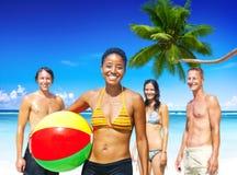 开心的年轻成人在一个热带海滩 免版税图库摄影