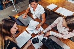 开快乐的女性的商务伙伴会议谈论销售战略在会议室 免版税库存照片