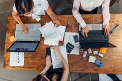 开快乐的女性的商务伙伴会议谈论销售战略在会议室 库存照片