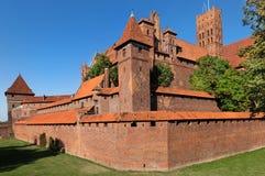 开户在河视图对面的砖瓦房城堡最大的malbork 库存照片