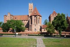 开户在河视图对面的砖瓦房城堡最大的malbork 图库摄影