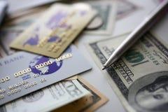 开户塑料说谎卡片和银色的笔在大相当数量美国金钱 免版税图库摄影