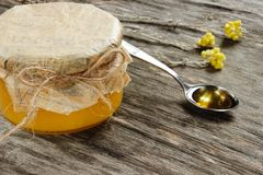 开户用与黄色干燥花的蜂蜜在灰色木背景 侧视图 库存图片