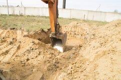 开掘一个深坑的桶挖掘机 库存照片