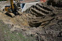 开掘一个深坑的毛虫挖掘的机器 免版税库存图片