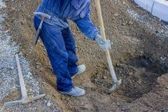 开掘与的建筑工人一个深刻的地下孔推 库存照片