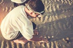 开掘亚裔的孩子获得乐趣在沙子 享用在b的年轻男孩 库存图片