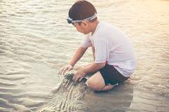 开掘亚裔的孩子获得乐趣在沙子 享用在b的年轻男孩 免版税库存图片