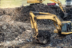 开掘入垃圾的工业挖掘机在都市垃圾堆积场 免版税库存图片