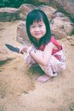 开掘可爱的亚裔的女孩获得乐趣在沙子在一个夏日 免版税库存图片