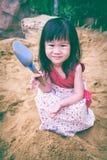 开掘可爱的亚裔的女孩获得乐趣在沙子在一个夏日 免版税库存照片
