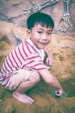 开掘可爱的亚裔的男孩获得乐趣在沙子在一个夏日 库存图片