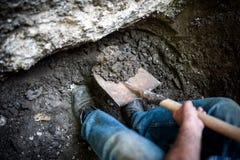 开掘在地面的男性一个孔与铁锹和锹 免版税图库摄影