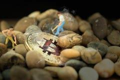 开掘在小卵石的微型人工作者金黄bitcoin 真正cryptocurrency采矿,电子货币交换,采矿 库存照片