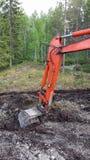 开掘在泥的橙色挖掘机胳膊 免版税库存图片