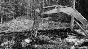 开掘在泥黑白照片的挖掘机胳膊 免版税库存图片
