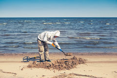 开掘在海滩的人一个孔 免版税库存照片