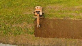开掘在领域的挖掘机一个沟槽 空中录影 库存图片