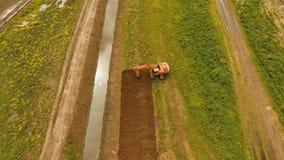 开掘在领域的挖掘机一个沟槽 空中录影 库存照片