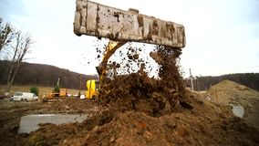 开掘坑和投掷土的挖掘者的慢动作 把地球扔出去挖掘机桶的特写镜头 射击 股票录像