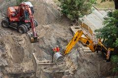开掘坑的挖掘机 水管修理  免版税库存图片