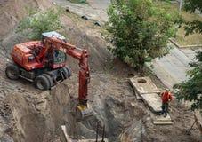 开掘坑的挖掘机 水管修理  免版税库存照片