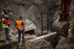 开掘坑的挖掘机 看在杓子的三名工作者 免版税库存图片