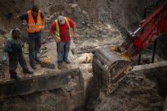 开掘坑的挖掘机 看在杓子的三名工作者 图库摄影