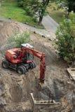 开掘坑的红色挖掘机 图库摄影